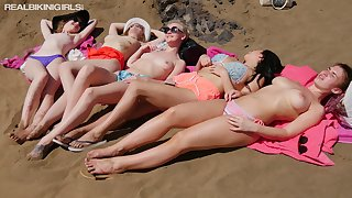 Several busty girlfriends are sunbathing topless